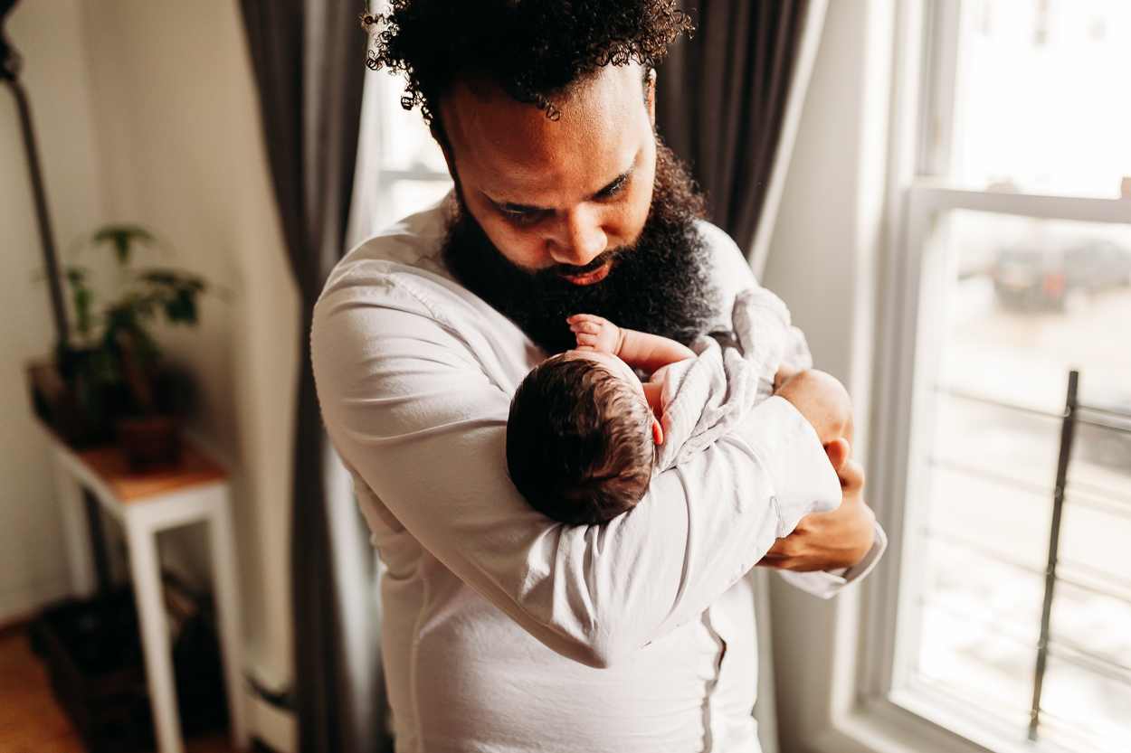 daddy holding newborn in his arms in home lifestyle newborn session