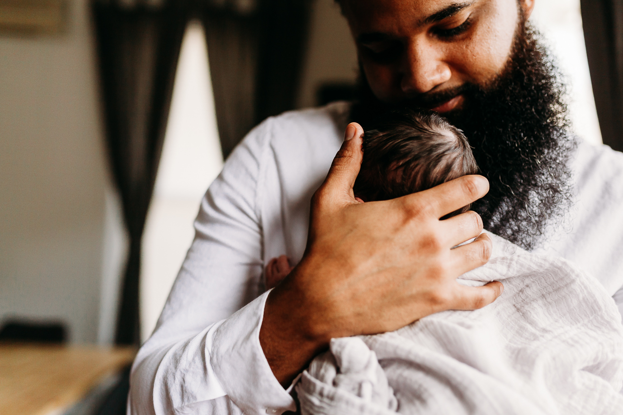 daddy cuddling his newborn in bronx newborn lifestyle session